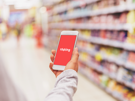 Person using Shping app in supermarket